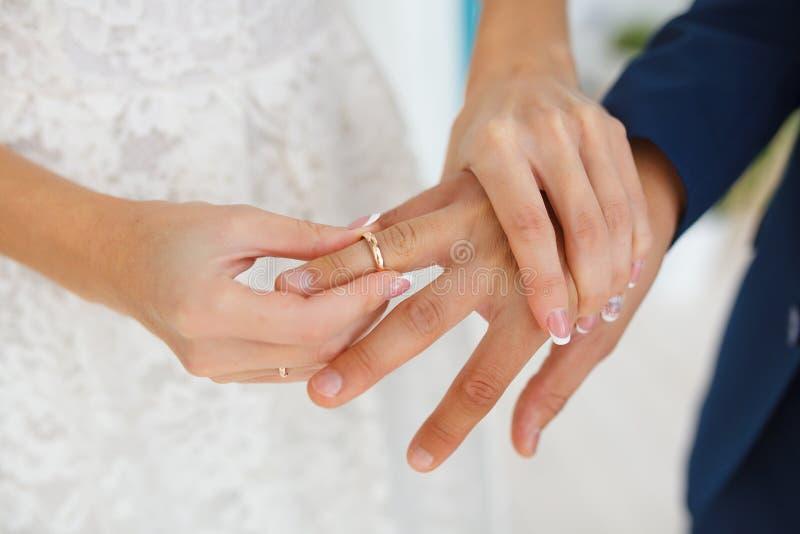 De bruid zet zorgvuldig de ring op de vinger van de toekomstige echtgenoot stock fotografie