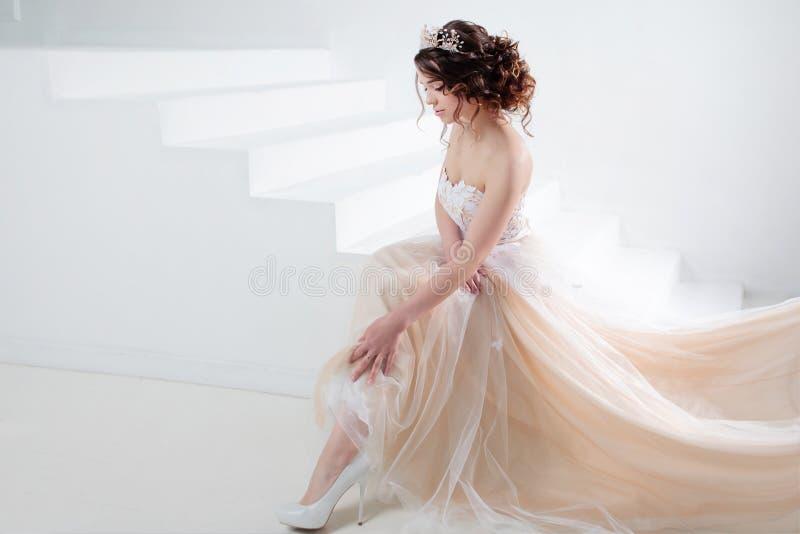 De bruid zit op de treden Portret van een mooi meisje in een huwelijkskleding Dansende Bruid, witte achtergrond royalty-vrije stock foto