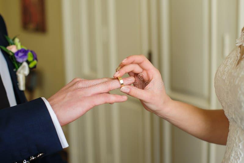 De bruidbruidegom zet de ring op zijn hand op de huwelijksdag stock afbeelding
