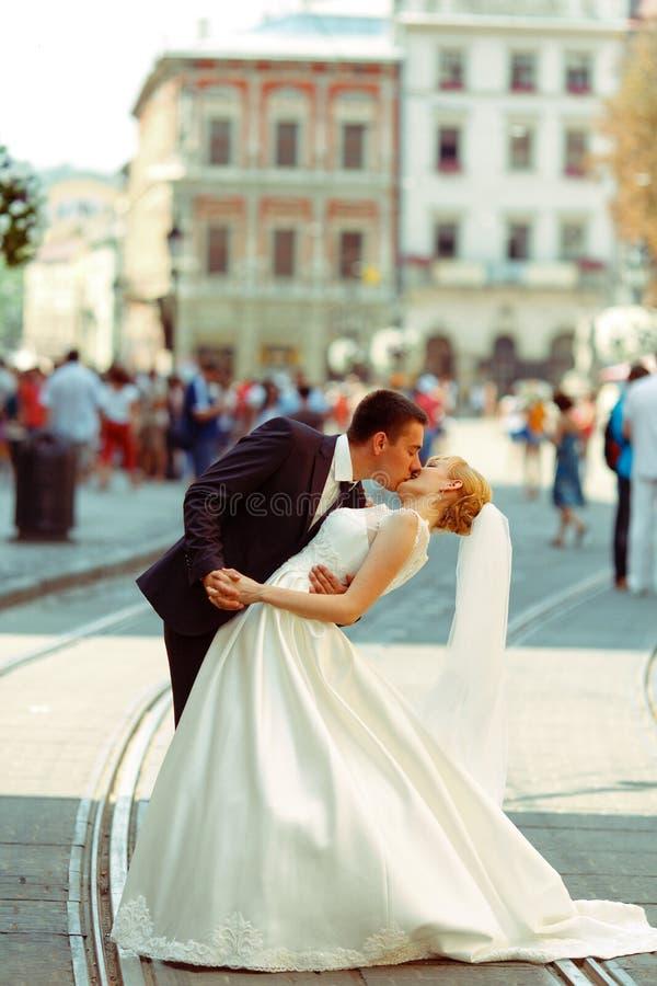 De bruidegom buigt bruid over het kussen van haar op een stadsvierkant royalty-vrije stock fotografie