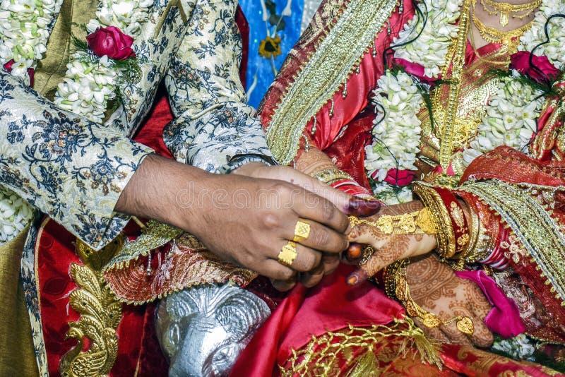 De bruidegom die de bruid dragen een trouwring op haar vinger stock afbeeldingen