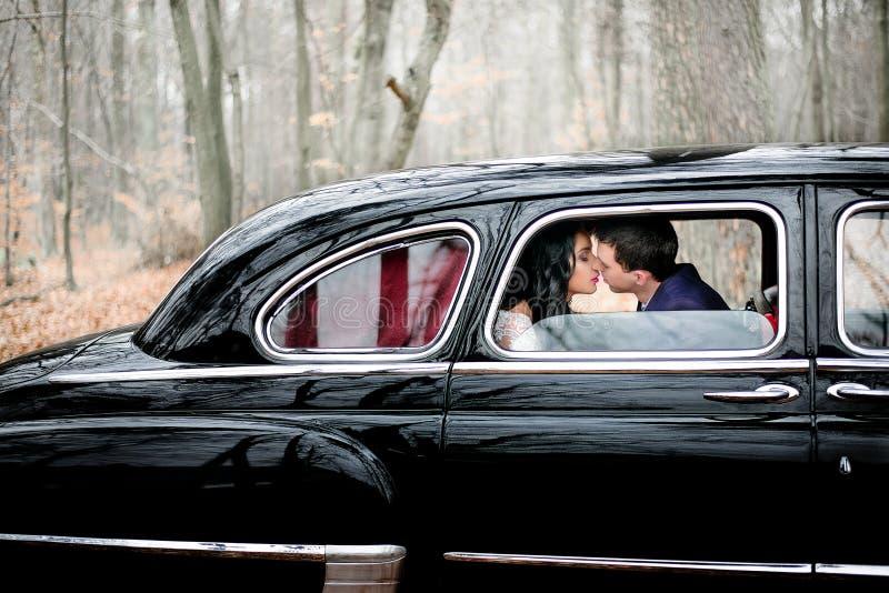 De bruidegom in donkerblauw jasje leunt aan bruid voor een kus stock afbeeldingen