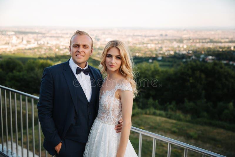 De bruidegom en de bruid bevinden zich op de achtergrond van de stad en drinken champagne van wijnglas Gerinkelglazen royalty-vrije stock foto's