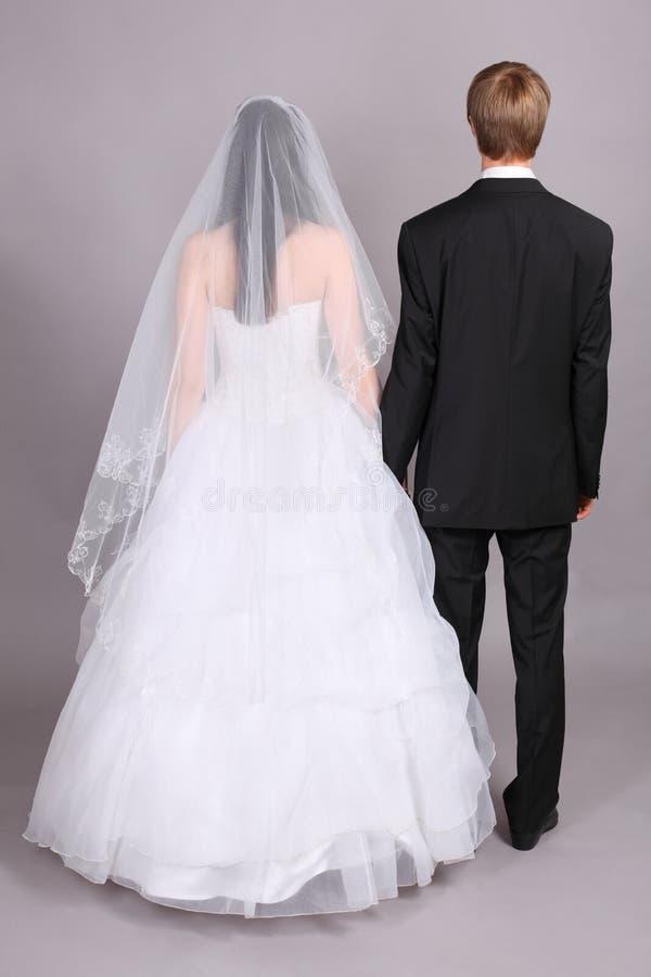 De bruidegom en de bruid bevinden zich hun ruggen aan camera royalty-vrije stock afbeelding