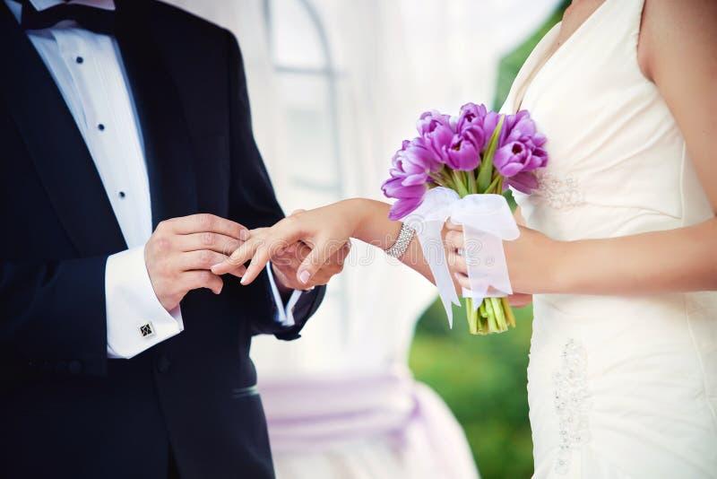 De bruidegom en de bruid tijdens huwelijksceremonie, sluiten omhoog op handen Huwelijkspaar en openluchthuwelijksceremonie stock foto's