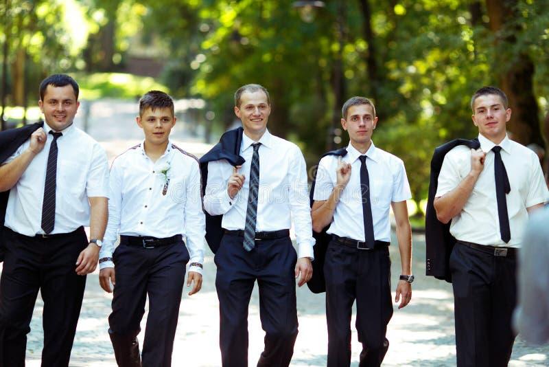 De bruidegom en groomsmen lopen trotse holding hun jasjes over zouden moeten stock afbeeldingen