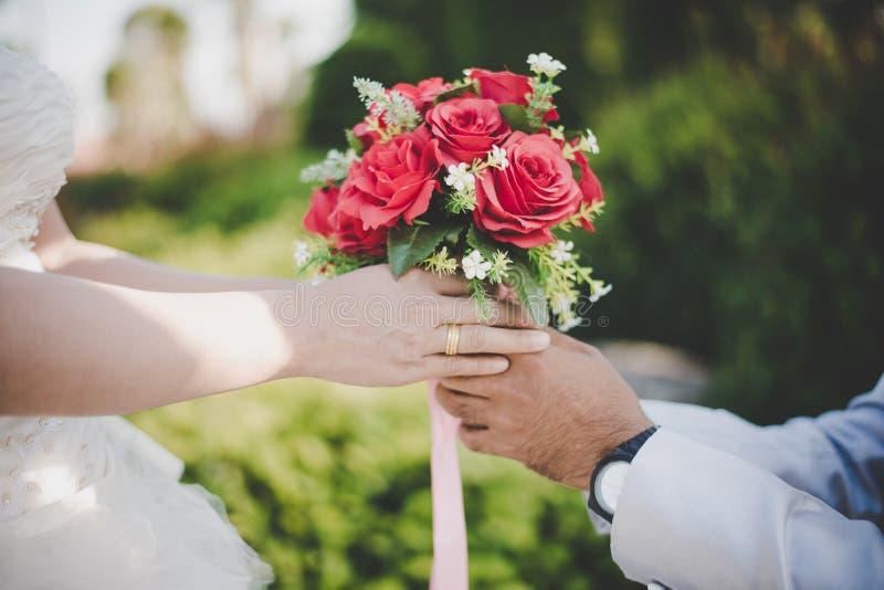 De bruidegom geeft boeket aan de bruid met aard royalty-vrije stock afbeelding