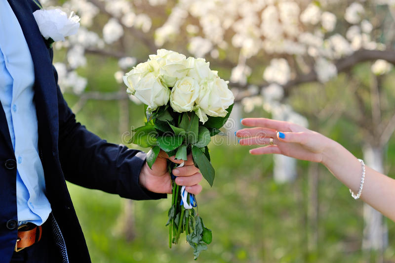 De bruidegom geeft de bruid een mooi huwelijksboeket stock fotografie