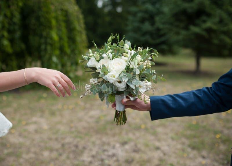 De bruidegom geeft de bruid een mooi huwelijksboeket royalty-vrije stock foto's