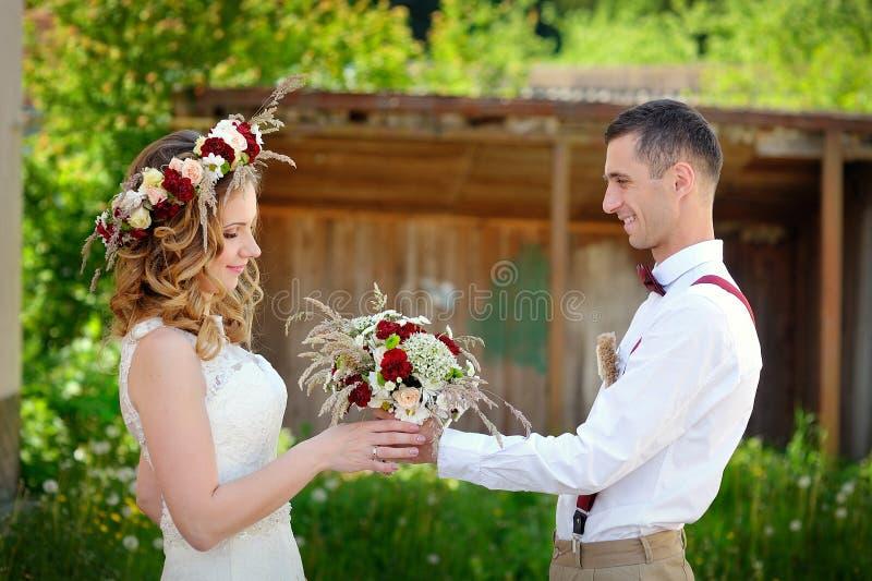 De bruidegom geeft het boeket van het bruidhuwelijk stock fotografie