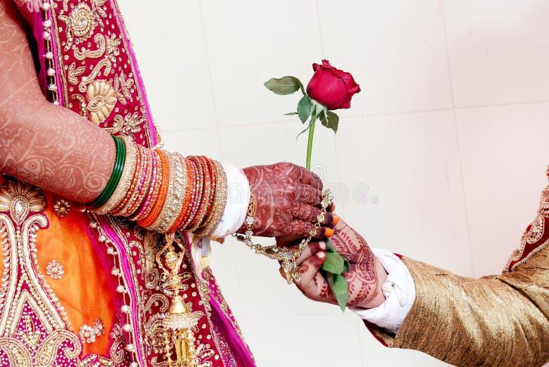 De bruidegom geeft toenam bloem tot bruid stock afbeelding