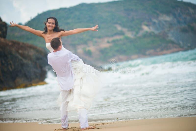 De bruidegom hief de bruid op, wat hand in hand uitspreidden paar in liefde op een verlaten strand door het overzees royalty-vrije stock foto's
