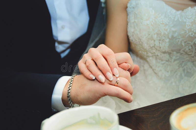De bruidegom houdt de bruid door de hand op de huwelijksdag Close-up stock fotografie