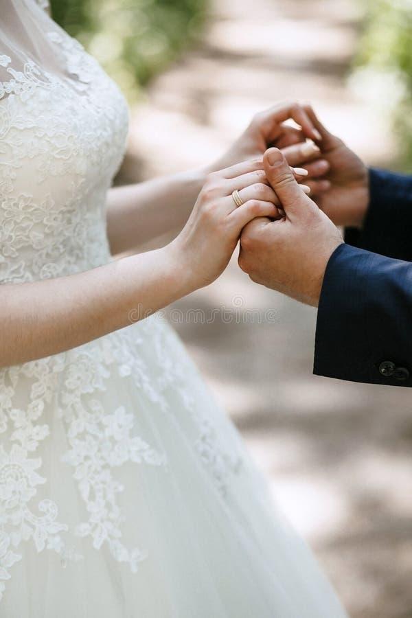 De bruidegom houdt de bruid ` s een huwelijkskleding met een mooie manicure en een trouwring indient royalty-vrije stock afbeeldingen
