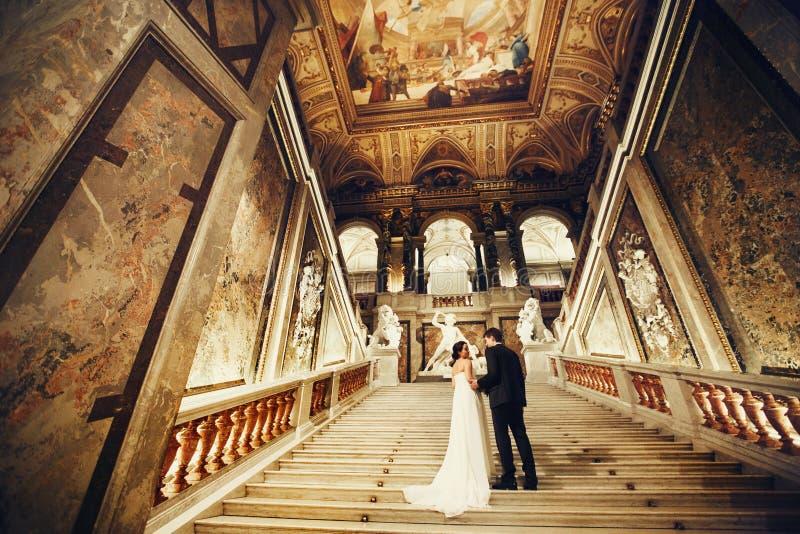 De bruidegom houdt bruid` s hand zich bevindt op de treden in geschilderde zaal stock afbeelding