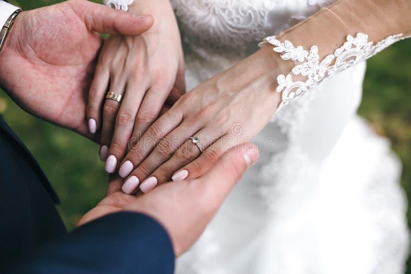 De bruidegom houdt de bruid` s handen met een mooie manicure en een verlovingsring met edelsteen royalty-vrije stock foto's