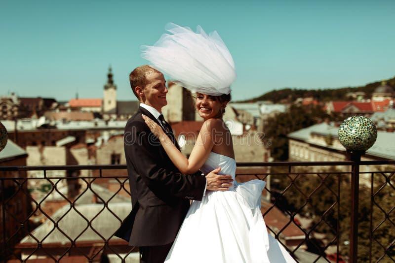 De bruidegom houdt een glimlachende bruid in zijn wapens op het dak in oud ci stock foto's