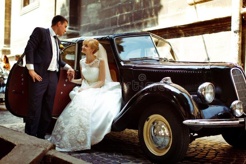 De bruidegom houdt een wapen van een charmante bruid terwijl zij in open zit royalty-vrije stock afbeelding