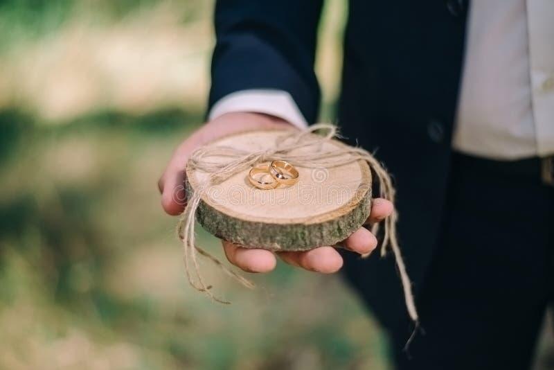 De bruidegom houdt houten tribune met gouden bruiloftringen stock afbeeldingen