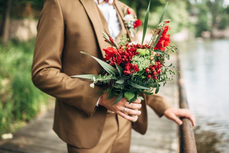 De bruidegom houdt huwelijksboeket met rode bloemen en greens royalty-vrije stock afbeeldingen