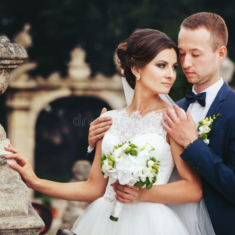 De bruidegom houdt schouders van het overweldigende bruid stellen op de oude rug royalty-vrije stock afbeelding