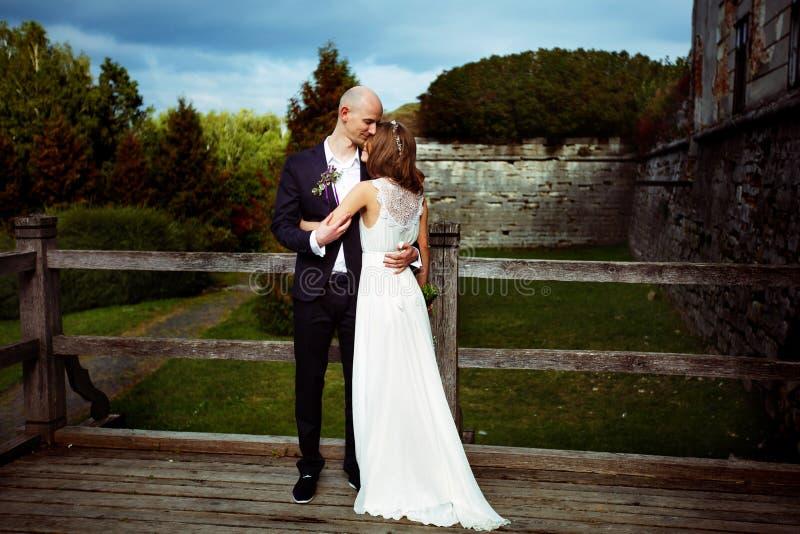 De bruidegom houdt teder bruid in zijn wapens die zich op oude houten bevinden stock foto