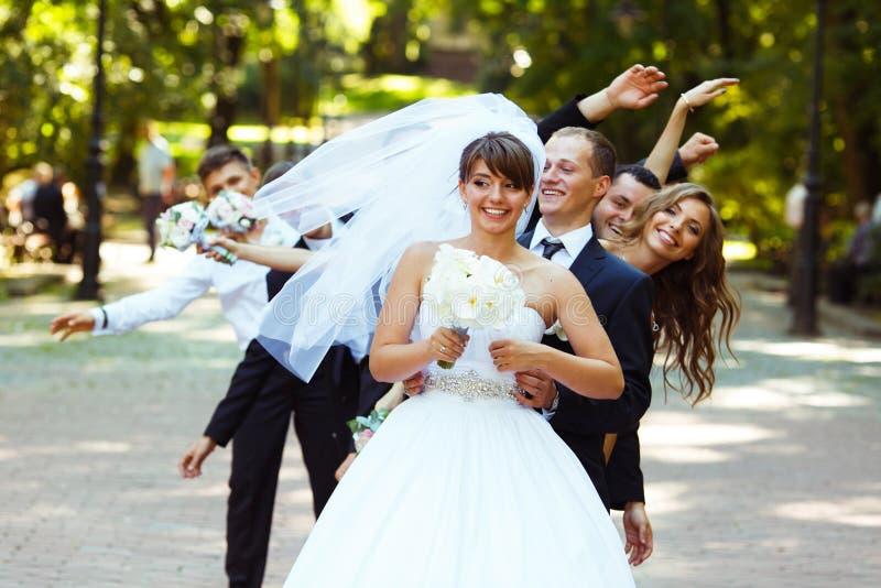 De bruidegom kijkt grappig terwijl de vrienden achter haar dansen stock fotografie