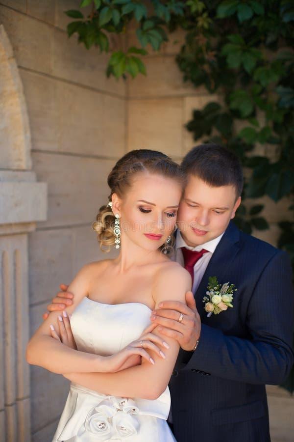 De bruidegom koesterde zacht de bruid op de straat royalty-vrije stock afbeelding