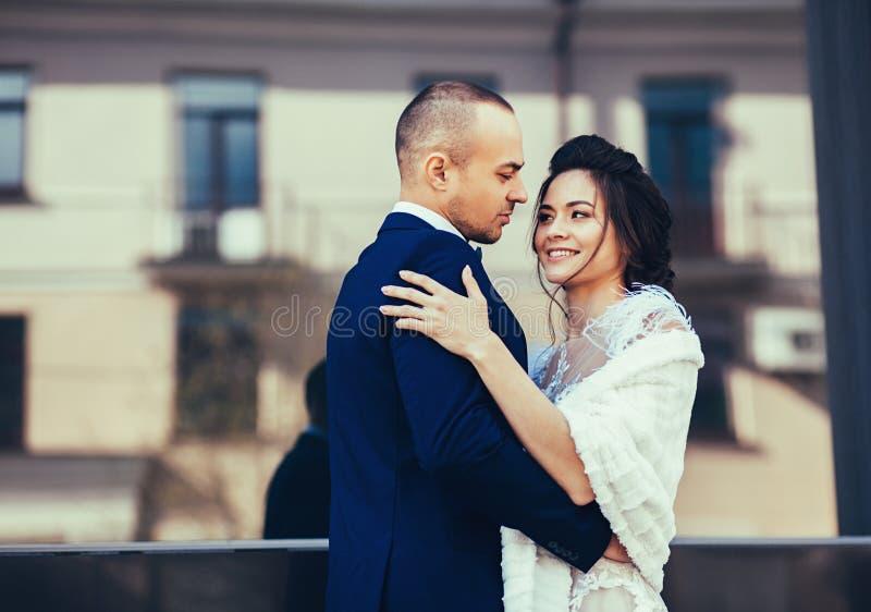 De bruidegom koestert overweldigende bruid royalty-vrije stock foto's