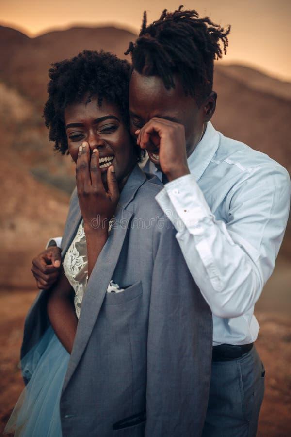 De bruidegom koestert zijn bruid gekleed in zijn jasje in canion bij zonsondergang a stock afbeelding