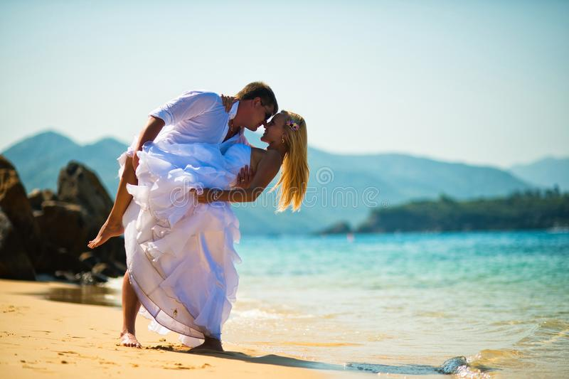 De bruidegom kust de bruid in mooi stelt op het strand tegen het overzees royalty-vrije stock afbeelding