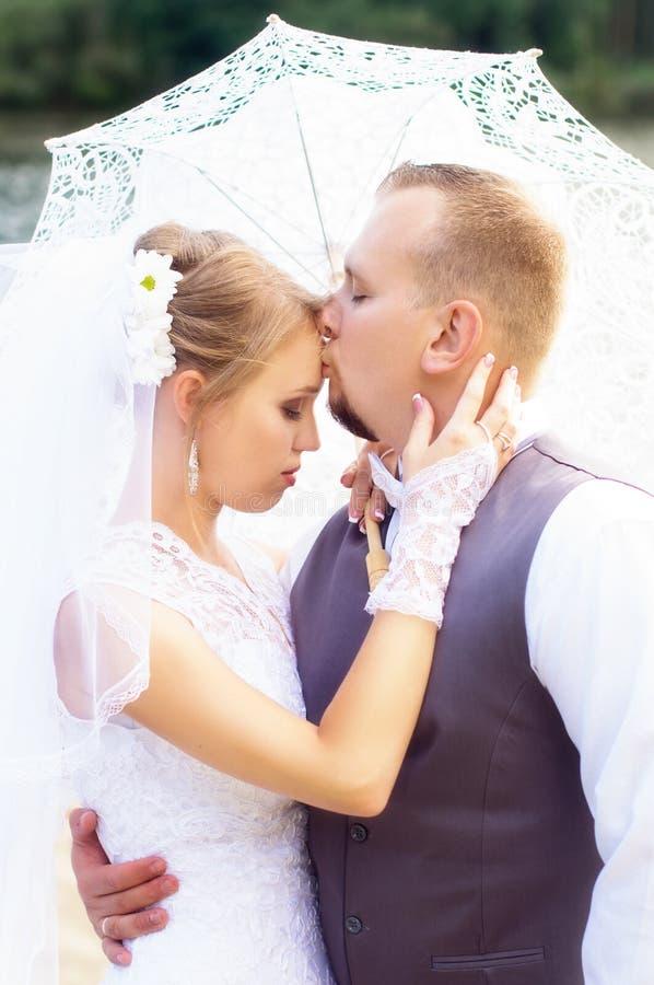 De bruidegom kust de bruid op het voorhoofd royalty-vrije stock foto's