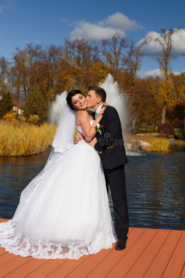 De bruidegom kust teder de bruid in de hals die zich op de pijler bevinden stock foto