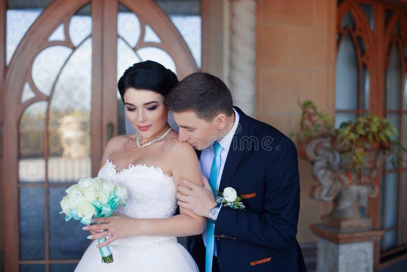 De bruidegom kust zacht de bruid in de schouder stock foto