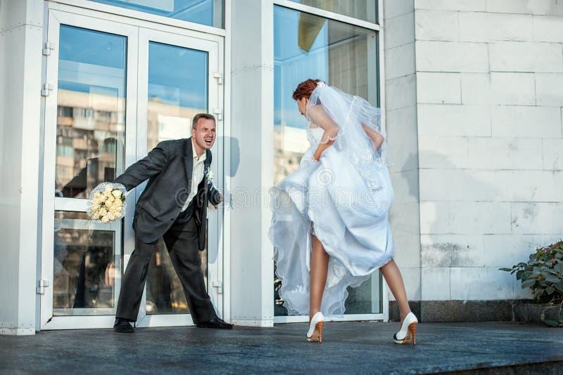De bruidegom laat niet de bruid bij een huwelijk stock afbeeldingen
