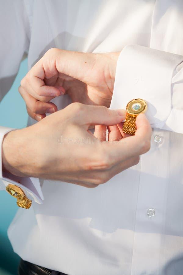 De bruidegom maakt manchetten recht royalty-vrije stock afbeeldingen