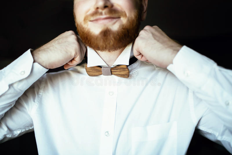 De bruidegom met baard kleedt de houten vlinderdas op huwelijksdag stock foto's