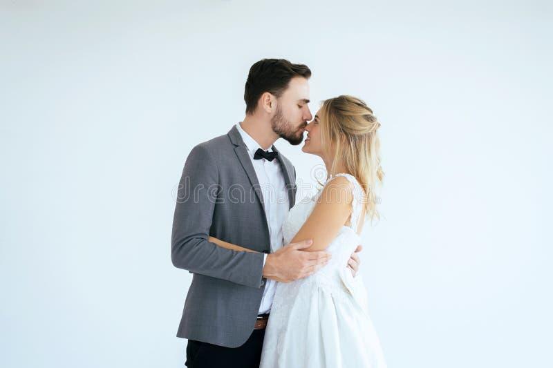 De bruidegom met bruid romantisch paar kust en koestert samen op witte achtergrond, het Positieve denken in huwelijksdag, Exempla stock foto