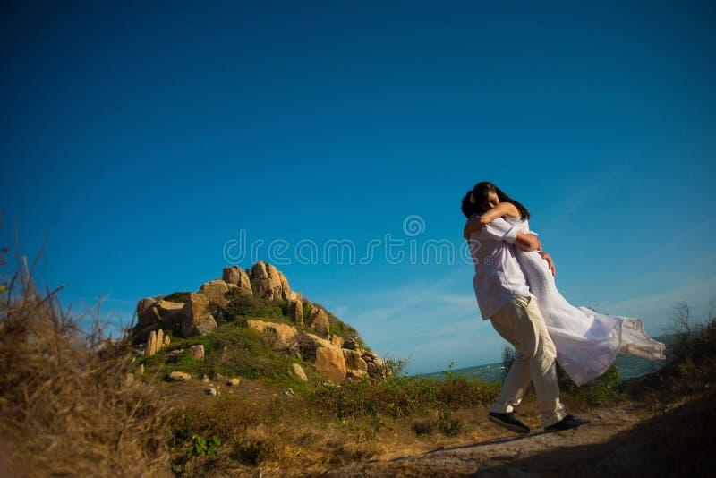 De bruidegom omcirkelt de bruid in zijn wapens tegen de bergen en de hemel stock foto's