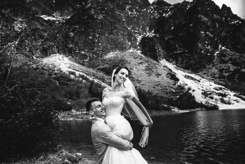 De bruidegom omcirkelt zijn jonge bruid, op de kust van het meer Morskie Oko polen De Zwart-witte foto van Peking, China stock afbeelding