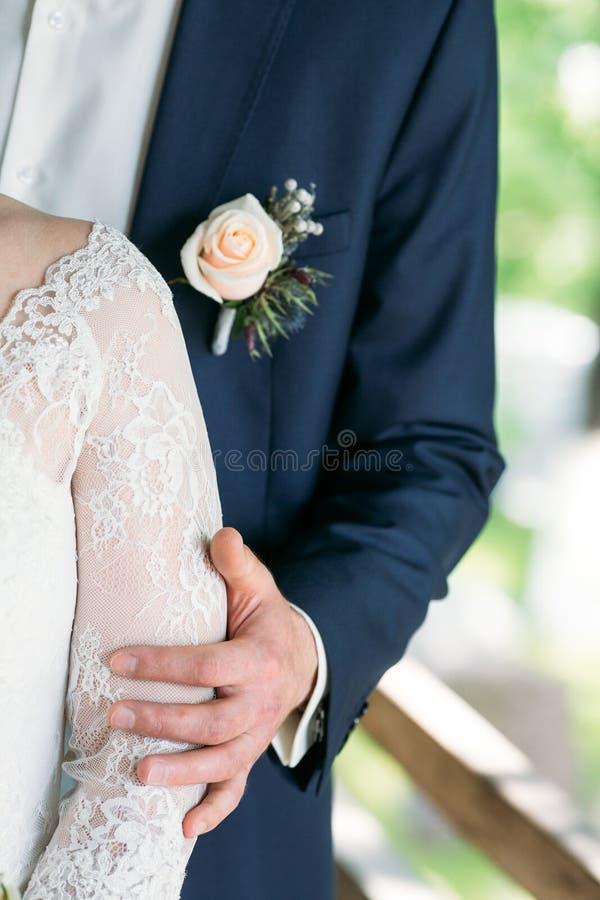 De bruidegom omhelst de bruid` s schouder stock fotografie