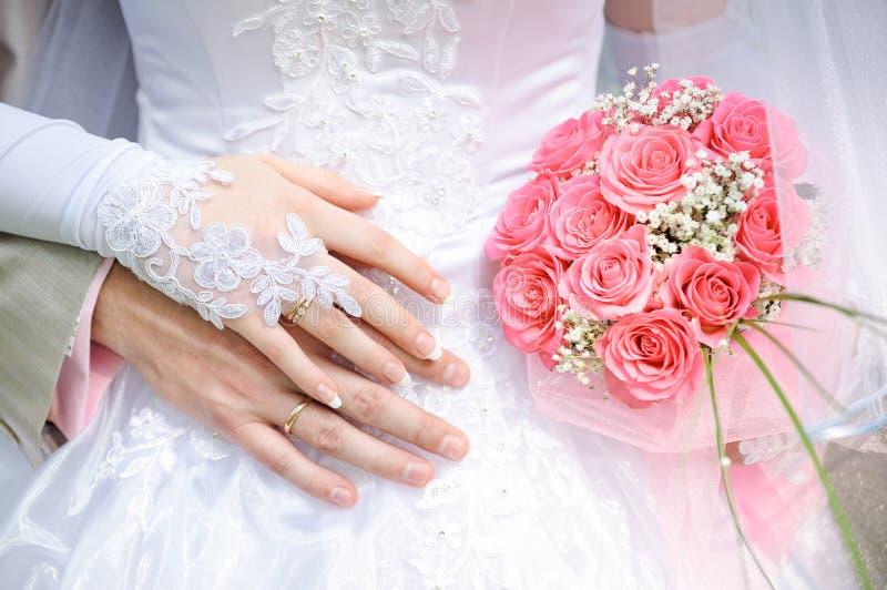 De bruidegom omhelst de bruid, houdt de bruid een huwelijksboeket royalty-vrije stock afbeelding