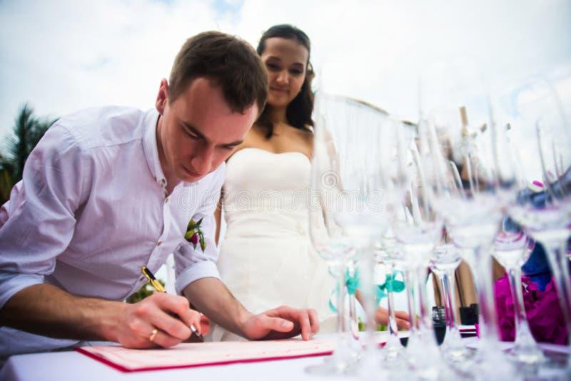 De bruidegom ondertekent documenten op registratie van huwelijk Een jong paar ondertekent de huwelijksdocumenten Openlucht huweli stock foto