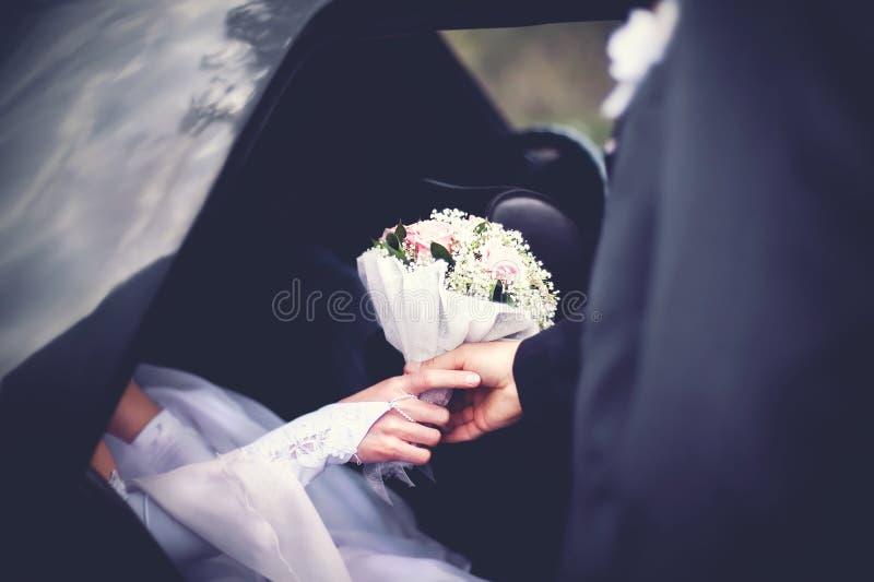 De bruidegom ontmoet bruid van de auto met huwelijksboeket van bloemen stock fotografie