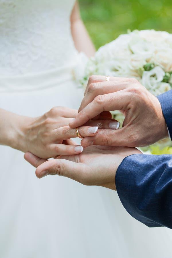 De bruidegom plaatst de ring op bride& x27; s hand De close-up van de foto royalty-vrije stock foto's