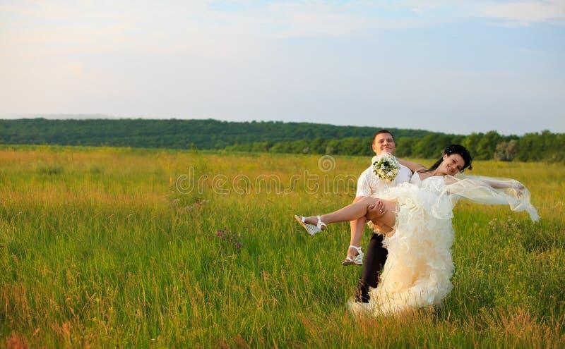 De bruidegom vervoert bruid op wapens stock fotografie