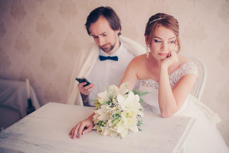 De bruidegom wordt afgeleid met de telefoon bij huwelijksphotosession royalty-vrije stock fotografie