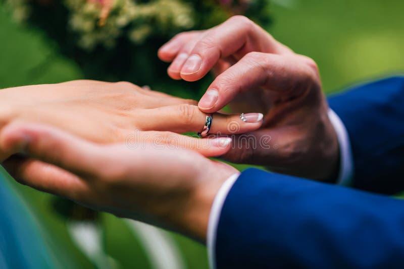 De bruidegom zet de bruid een trouwring van witgoud op zijn vinger stock foto's