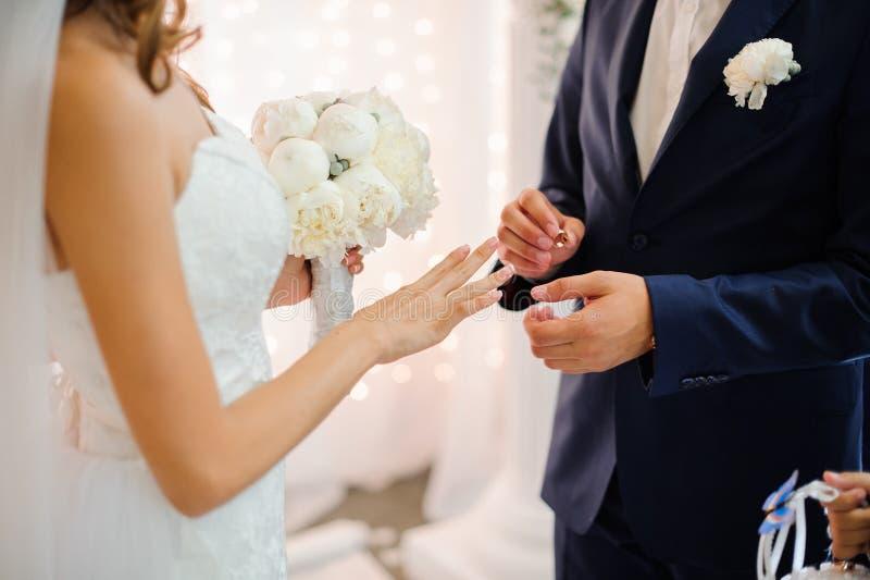 De bruidegom zet op een gouden trouwring op de vinger van een mooie bruid royalty-vrije stock foto