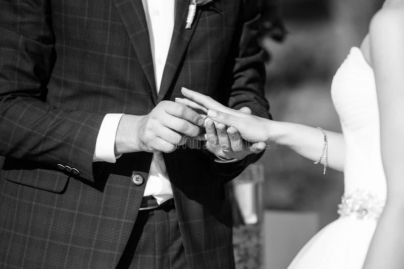 De bruidegom zet de trouwring op bruid dichte omhooggaand De bruid zet de bruidegom op de trouwring stock fotografie